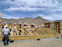 A team raises a wall of a new home sponsored by the U.S. Department of Housing and Urban Development