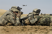 Two U.S. Army soldiers use binoculars and a riflescope to watch for insurgents