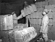 "Red Ball Express troops stack ""jerry cans"" used to transport gasoline to front-line units during World War II."
