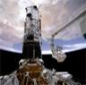 Astronauts Musgrave and Hoffman install corrective optics during the Hubble Telescope's Service Mission 1