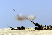 A 155 mm artillery shell is visible as it exits the barrel of an M-198 howitzer during training
