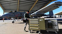 An aircraft armament technician pushes a 500-pound toolbox to an A-10 at Whiteman Air Force Base