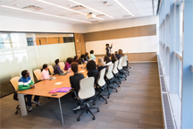 A meeting held in a long conference room.