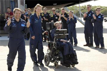 Well-wishers greet physicist Stephen Hawking (in wheelchair) at the Kennedy Space Center Shuttle Landing Facility