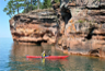 Kayakers enjoy exploring Apostle Islands' sea caves on calm Lake Superior