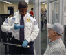 A TSA Officer screening a passenger
